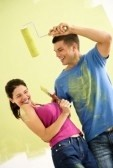 2043649-attractive-couple-standing-in-front-of-partially-painted-wall-playfully-putting-paint-on-eachother